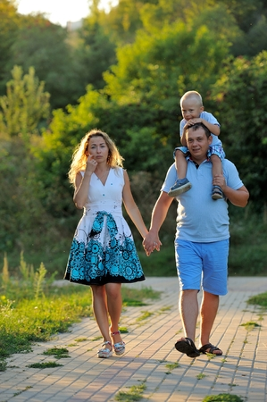 The family holds hands and walks along the paths in the Park at sunset on a summer day. The child sits on the neck of his father. Family walk in nature. Portrait. Vertical view. Imagens