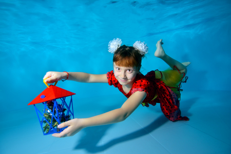 A little girl swims underwater in the pool with her eyes open near the bottom in a red dress, holding a gift in her outstretched hand and smiling. Portrait. Horizontal view.