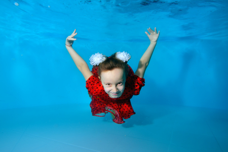 Smiling little girl swims and dives underwater in the pool with her eyes open in red dress on blue background. Portrait. Horizontal view.