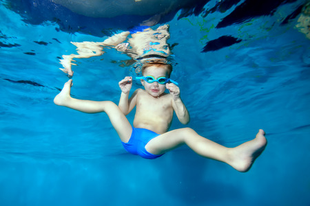 A little boy swims and plays underwater in the pool with his legs spread out to the sides and looks at the camera. Portrait. Underwater photography. Horizontal orientation of the image.