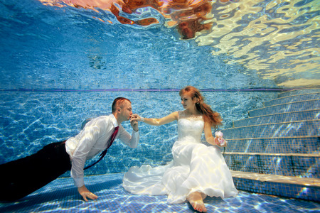 A sweet bride in a white dress sits under the water at the bottom of the pool, and the groom kisses her hand. They are illuminated under water by sunlight. Portrait. Concept. Wedding underwater.