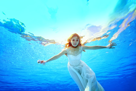Cute bride swims and poses for the camera under the water in the pool in a white dress, arms outstretched on a Sunny day. Portrait. Bottom view of the water surface. Underwater photography.