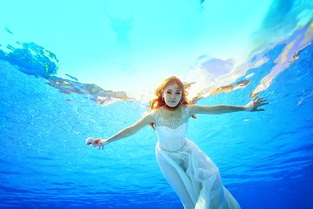 Jolie mariée nage et pose pour la caméra sous l'eau dans la piscine dans une robe blanche, les bras tendus par une journée ensoleillée. Portrait. Vue de dessous de la surface de l'eau. Photographie sous-marine.