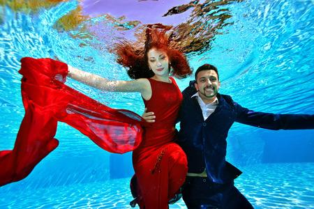 De bruid en bruidegom in een rode jurk met rood haar zwemmen en spelen onder water in het zwembad op een zonnige dag. Ze glimlachen en poseren voor de camera op een blauwe achtergrond. Portret. Bruiloft onderwater fotograferen. Stockfoto