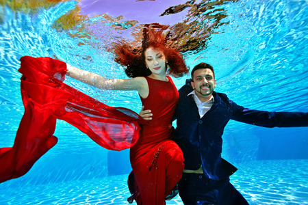 The bride and groom in a red dress with red hair swim and play underwater in the pool on a Sunny day. They smile and pose for the camera on a blue background. Portrait. Wedding underwater shooting. Banco de Imagens