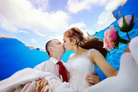 Encantadora novia con flores en la mano y el novio besándose bajo el agua en el fondo de nubes en la superficie. Retrato. De cerca. Vista desde abajo. Fotografía submarina. Vista horizontal.