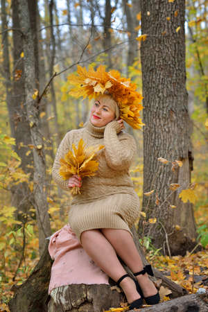 A sweet woman, a middle-aged blonde in autumn leaves, with a wreath on her head, sitting on a stump in the autumn forest in a gentle jumper. Size plus xxl female. Vertical view.