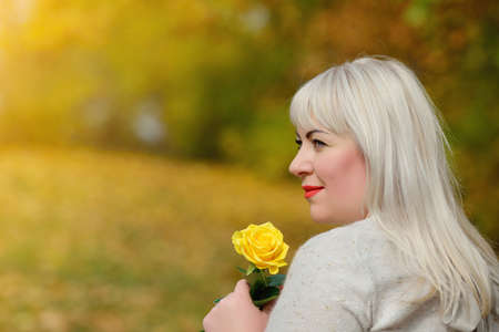 Portrait of a cute middle-aged blonde woman outdoors. She stands and poses with a yellow rose in her hand in the Park on a Sunny autumn day. She looks away and smiles. Profile. Close-up.