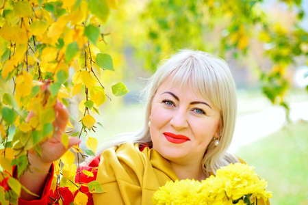 Fashionable portrait of blonde woman plus size outdoors. She stands in the autumn near a tree with yellow leaves in a red cloak, looking at the camera and smiling. Close-up.