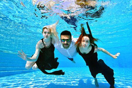 Zwei junge Mädchen, eine Blondine und eine Rothaarige, schwimmen und posieren unter Wasser und umarmen einen Mann östlicher Nationalität mit Sonnenbrille. Mädchen in Kleidern, ein Typ in einem weißen Hemd. Modeporträt