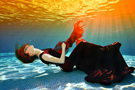 Beautiful young girl lying at the bottom of the pool. She lies with her eyes closed in a burgundy dress, her red hair against the sunlight from the surface. Surrealism. Concept. Landscape orientation.