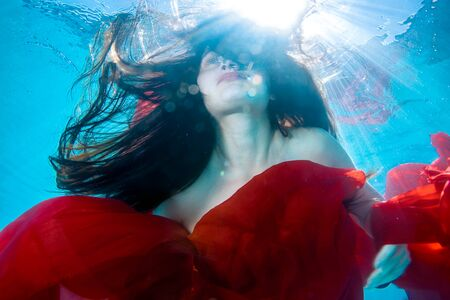Surreal underwater portrait of a beautiful girl with loose hair, which floats under the water with a red cloth in his hands on the background of the rays of light. Fashion portrait. Close up.