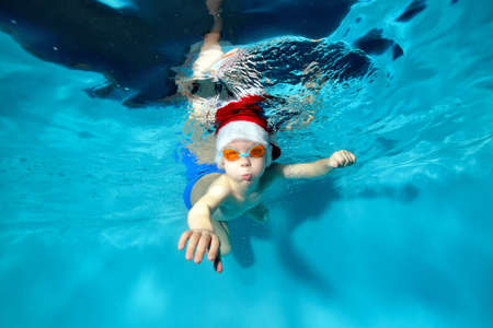 Happy little boy swims underwater in Santa's red hat and swimming glasses. He looks into the camera and blows bubbles. Portrait. Concept. Underwater photography.