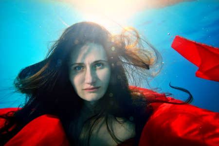 Unusual girl under the water thoughtfully looks at the camera and posing with a red cloth, with her hair down, against the background of sunlight from the surface. Portrait. Underwater photography. Stok Fotoğraf