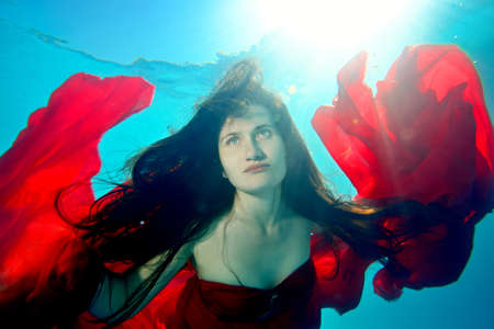 A beautiful, extraordinary girl swims under the water with a red cloth, with her hair down, her arms outstretched like a bird against the background of sunlight from the surface. Portrait. Close up. Stok Fotoğraf