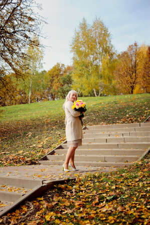 An adult blonde woman poses full-length, standing with a bouquet of yellow and pink roses on the stairs in the Park, against the background of autumn trees and looks at the camera. Vertical view Stok Fotoğraf