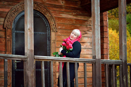 A plump middle-aged woman stands on the porch of an old wooden house in a red scarf and black dress, looking at the camera and smiling with red roses in her hands Stok Fotoğraf
