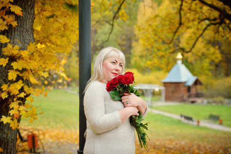 A plump middle-aged blonde with red roses in her hands poses against a beautiful rural landscape and a small wooden Church. Close-up. Horizontal view