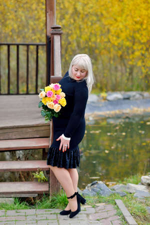 A nice big woman stands in a black dress and looks at her black shoes. She poses outdoors with a bouquet of yellow and pink roses in her hands. Fashion portrait. Vertical view Stok Fotoğraf