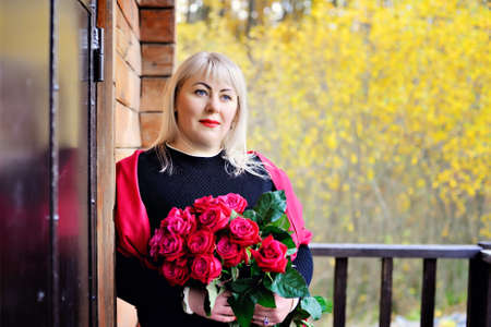 Portrait of a charming middle-aged blonde, large size, who is posing in nature near a wooden house with red roses in her hands against a background of yellow foliage. Closeup. Blurred background
