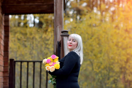 A plump middle-aged woman with a bouquet of yellow and pink roses poses in nature near a wooden house. She stands in a black dress and looks thoughtfully into the distance. Fashion portrait