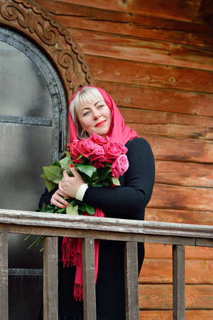 Portrait of a middle-aged woman, large size, who stands on the porch of a wooden house with red roses in her hands, in a red scarf and a black dress. Closeup