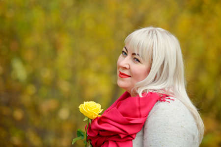 A playful woman of large size poses in a red scarf, with a yellow rose in her hands, outdoors, against a background of yellow trees. She looks into the distance and smiles. Conceptual portrait Stok Fotoğraf