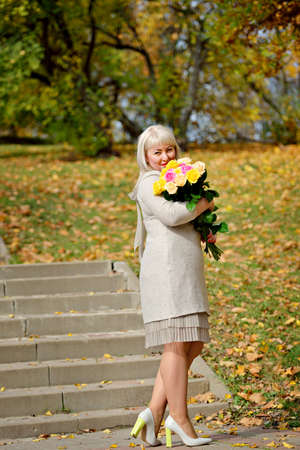 A middle-aged blonde woman stands and poses with a bouquet of yellow roses in a Park against autumn trees and looks at the camera. Fashion portrait. Vertical view Stok Fotoğraf