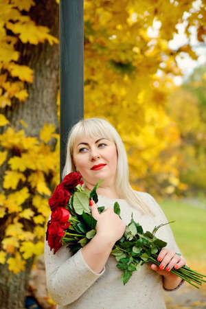 A dreamy, middle-aged, large-sized woman with red roses in her hands poses outdoors against a background of yellow foliage. Close-up. Vertical view Stok Fotoğraf