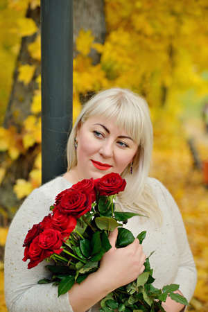 Portrait of a middle-aged woman, large size, with white hair, with red roses in her hands, posing in the open air against a background of yellow foliage. Closeup. Vertical view Stok Fotoğraf