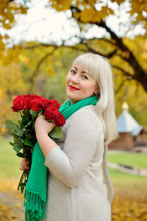 A plump middle-aged blonde woman stands and smiles in a green scarf and holding red roses in the nature, against the background of yellow autumn trees. She looks at the camera. Fashion portrait