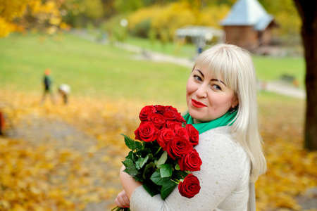 A sweet, plump middle-aged blonde stands and poses with red roses in her hands in nature against the background of yellow autumn trees. She looks away over her shoulder and smiles. Closeup