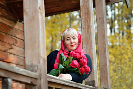 A middle-aged, large woman in a red scarf and black dress looks out from the porch of a wooden house with red roses in her hands against the background of autumn leaves. Closeup