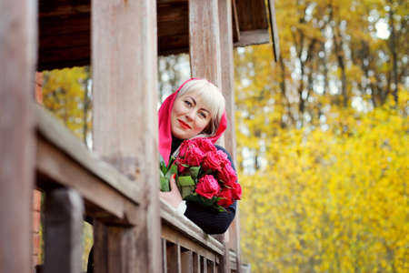 A cute middle-aged blonde in a red headscarf looks out from the porch of an old wooden house. She holds red roses and looks at the camera with a smile. Closeup