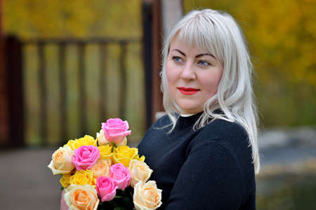 Portrait of a plump middle-aged woman with a bouquet of yellow and pink roses, who stands and poses in a black dress in nature against the background of autumn foliage. Fashion portrait