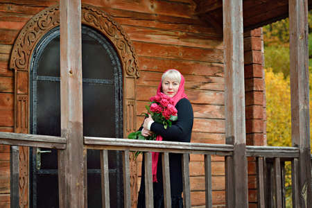A sad, middle-aged, large woman stands on the porch of a wooden house with red roses in her hands, wearing a red handkerchief and a black dress, and looks thoughtfully at the camera
