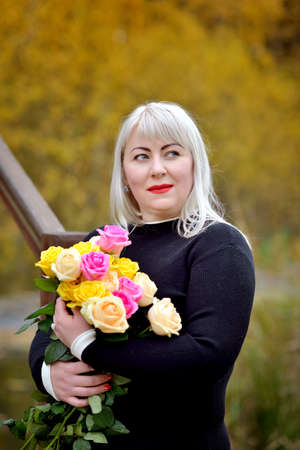 Close-up, a cute plus-size blonde woman poses in a black dress with a bouquet of yellow and pink roses in her hands outdoors. She smiles and looks away. Fashion portrait Stok Fotoğraf