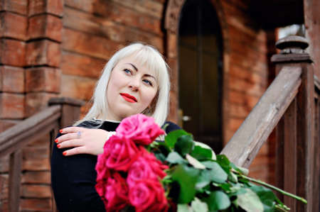 An adult plump blonde in a black dress stands with red roses in her hands, her head bowed and dreamily looking up, against the background of an old wooden house. Closeup