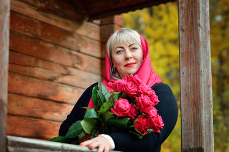 Portrait of a cute middle-aged blonde woman in a red scarf with red roses in her hands. She poses in nature on the porch of an old wooden house in a black dress. She smiles and looks at the camera