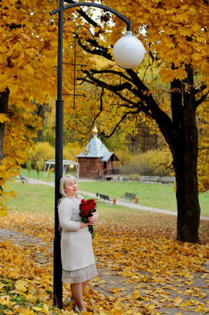 A middle-aged blonde woman stands leaning against a lantern in a city Park against a background of yellow autumn trees with red roses in her hands. She looks into the distance and smiles Stok Fotoğraf