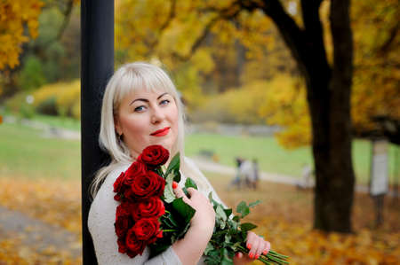 Portrait of a sweet, plump, middle-aged woman who looks at the camera with irony, standing in nature against a background of yellow trees with a bouquet of red roses in her hands. Closeup
