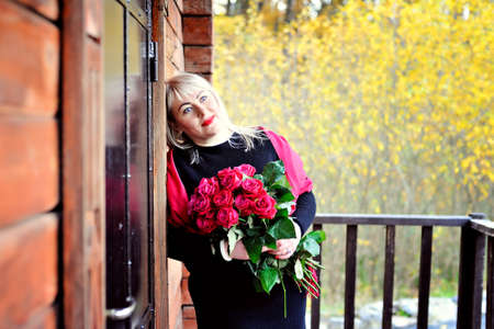A dreamy middle-aged woman, large in size, with white hair, poses outdoors near a wooden house with red roses in her hands against a background of yellow foliage. Closeup. Portrait Stok Fotoğraf