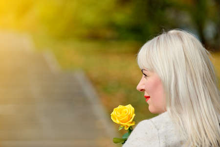 Portrait of a lovely middle-aged woman with a yellow rose in her hands. It stands in a Park on background of autumn trees and looking to the side. Fashion portrait. Profile. Closeup Stok Fotoğraf