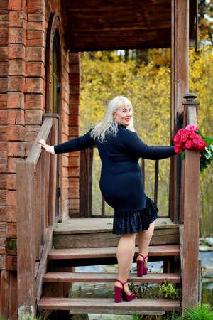 A plump, playful, middle-aged blonde stands and poses in a black dress on the stairs of an old wooden house, smiling and looking over her shoulder at the camera. Vertical view