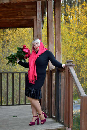 A plump middle-aged woman in a red headscarf and black dress stands and poses on the porch of an old wooden house. She smiles and looks at the camera with a bouquet of red roses in her hands Stok Fotoğraf