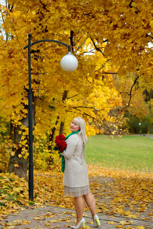 A plump middle-aged woman poses in an autumn Park against a background of yellow trees with red roses in her hands. She looks at the camera and smiles. Vertical view