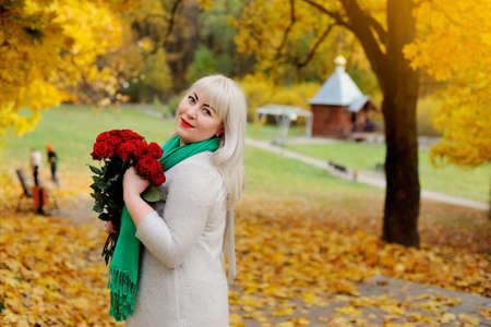 An adult woman of middle age, large size, stands and smiles with red roses in her hands in nature, against the background of yellow autumn trees. She looks over her shoulder at the camera and smiles