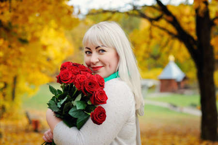 Portrait of a sweet, plump middle-aged woman posing with red roses in her hands in an autumn Park against a background of yellow trees. She looks at the camera and smiles. Closeup