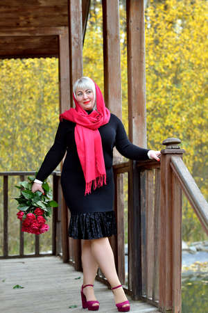 A charming plump middle-aged woman in a red headscarf poses in nature on the porch of an old wooden house in a black dress. She smiles and looks away with a bunch of red roses in her hands