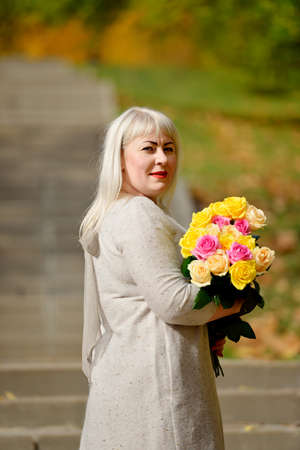 A large blonde woman stands and poses with a bouquet of yellow and pink roses in a Park, outdoors, against a background of trees and looks at the camera over her shoulder. Fashion portrait